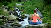 postoj : Woman meditating at tropical waterfall
