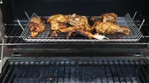 Grilled Tandoori Chicken marinated with yogurt, garlic , ginger, and exotic spices cooking on a barbecue grill.