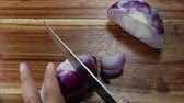 Chopping red Onions on a wooden board Stock Footage