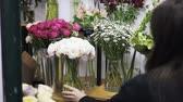 handheld : Close up of a woman florist putting vases with different beautiful flowers on shop shelves. Handheld real time close up shot