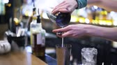 cubo de gelo : Close up of an unrecognizable bartender pouring yellow juice into a metal shaker while standing behind a bar stand. Side view. Handheld real time close up shot Vídeos