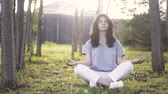 meditate : Portrait of a young woman wearing white pants and a gray T shirt meditating on a lawn in a park. Locked down real time medium shot