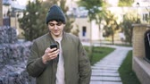 chillout : Close up of a young man wearing a dark green vest and a beanie standing in a park and surfing the net from his smartphone. Locked down real time close up shot