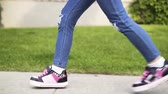 inline : Side view of an unrecognizable girl wearing blue jeans roller skating in a park. Concept of a summer vacations. Handheld real time close up shot