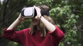fogaskerekek : Young woman wearing a red sweater is using VR glasses while being at a park near large tree. Handheld real time close up shot Stock mozgókép