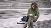 high quality : Pretty young woman is sitting on wooden stairs outdoors and drawing at her tablet computer with a special pen. Locked down real time establishing shot