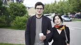 magánélet : Young couple consisting of a handsome man in glasses and a charming Asian woman is walking in a street and looking to the camera. Tracking real time establishing shot