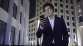 enviar : Attractive young businessman wearing a suit and glasses is looking at his cell phone screen and walking. He is serious and concerned. Tracking real time establishing shot Vídeos
