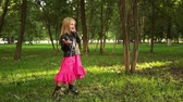 promotional : Cute little blonde girl wearing a leather jacket and a pink dress listening to the music standing in a park on a summer day. Locked down real time medium shot