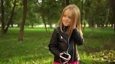 promocional : Cute little blonde girl wearing a leather jacket listening to the music standing in a park on a summer day. Locked down real time medium shot