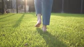 bare : Unrecognizable young woman walking on the grass barefoot. Concept of freedom and enjoying one s life. Tracking real time medium shot