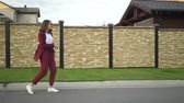 Pretty young woman wearing a suit is dancing in the street on a cloudy day. Tracking slow motion medium shot