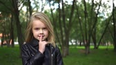 Cute little girl wearing a leather jacket making a hush sign standing in a park. Handheld real time medium shot