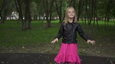 Cute little blonde girl wearing a leather jacket and a pink dress listening to the music standing in a park on a summer day. Zoom out real time medium shot