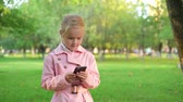Little girl in a pink coat texting during her walk in a park on a sunny day. Tracking slow motion establishing shot Stock Footage