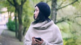 Attractive young Asian woman wearing a sweater and a beret is holding her smartphone and looking around with a dreamy smile. Handheld slow motion medium shot