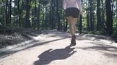 Rear view of legs of an unrecognizable jogger woman in dark red running shoes running on a road in a park on a sunny day. Tilt up slow motion medium shot