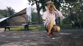 haarband : Woman jogger with blonde curly hair using a hairband and starting her workout in the street. Handheld slow motion medium shot Stockvideo