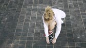 ayakkabı bağı : Top view of an unrecognizable jogger woman with blonde hair tying her shoelace, taking her smartphone with headphones and starting to run in a park. Handheld slow motion close up shot Stok Video