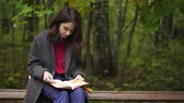 Calm young brunette woman wearing a coat, gloves and a beret is reading a book sitting on a bench in an autumn park. Handheld slow motion medium shot