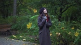 Cheerful young woman wearing a thick coat, gloves and a beret is holding a book with maple leaves and smiling while walking under falling leaves. Handheld slow motion tracking shot Stock Footage