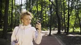 maraton : Beautiful blonde video blogger jogging in a park and shooting her workout in the process. Tracking slow motion medium shot Wideo