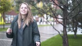 iyi bir ruh hali : Happy young woman with fair hair wearing a coat and holding a bag is dancing in an autumn street. Handheld slow motion medium shot