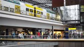 triumphal arch : BERLIN - AUGUST 21: Real time locked down medium shot of a tourist crowd at the Berlin Central Station, August 21, 2017, Germany. A white and yellow train leaving.