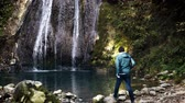 distante : Rear view of a young dark haired tourist admiring a beautiful waterfall in a forest on an autumn day. Locked down real time medium shot Stock Footage