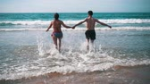 slomo : Happy Couple Having Fun on Ocean Waves, slow motion Stock Footage