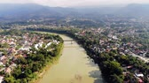 Aerial view of Luang Prabang and surrounding lush mountains of Laos. Nam Kahn River, a tributary of the Mekong River, flows peacefully on the right. Videos