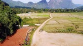 laosz : Blue lagoon, Vang vieng, Laos. flying over rice fields on the background of high mountains and hills