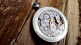 clock dial : Clock mechanism on a wooden background. Stock Footage