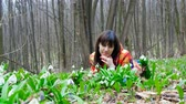 stink : A beautiful woman enjoys blossoming snowdrops in a spring forest
