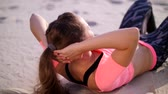 mind body soul : Healthy, young beautiful woman performs exercises for muscles of the press, picks up the body, pumps the press lying on the sand, on the beach, at sunrise