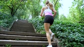 sleepers : Beautiful sexy athletic young blond woman in a T-shirt and shorts, runs upstairs, in the forest, park, in summer day. Bottom view, from the back. Slow motion Stock Footage