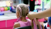 working parents : Beautiful blond girl, of seven years old, braided two pigtails, do a hairstyle with pink locks of hair in a beauty salon, a hairdressers salon, in front of a large mirror. a little princess