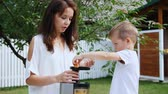 family values : summer, in the garden. mother and four-year-old son make fresh juice of mandarins, put mandarin slices in a juicer
