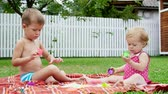 family values : small children, a four-year-old boy and a one-year-old girl, brother and sister, play together, paint with finger paints, in the garden, sitting on a blanket, on grass, lawn, in summer