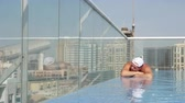 близнецы : DUBAI, UNITED ARAB EMIRATES, UAE - NOVEMBER 20, 2017: near Mall of the Emirates, al khoory hotel swimming roof pool, Caucasian Traveler man relax, swim, enjoy urban view Стоковые видеозаписи