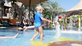 wadi : DUBAI, UNITED ARAB EMIRATES, UAE - NOVEMBER 20, 2017: Hotel Jumeirah Al Qasr Madinat, childrens water park, a little boy playing with fountains,in a pool for small children, babies