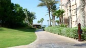 madinat : DUBAI, UNITED ARAB EMIRATES, UAE - NOVEMBER 20, 2017: Hotel Jumeirah Al Qasr Madinat , morning walk around the hotel on a bus-bug, all the greens are in the sunshine Stock Footage