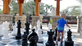 estratégico : DUBAI, UNITED ARAB EMIRATES, UAE - NOVEMBER 20, 2017: Hotel Jumeirah Al Qasr Madinat , baby boy playing big outdoors chess on a large chessboard
