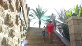 madinat : DUBAI, UNITED ARAB EMIRATES, UAE - NOVEMBER 20, 2017: Hotel Jumeirah Al Qasr Madinat , mom and son walking around hotel, descend the stairs in the rays of the sun