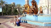 arab : DUBAI, UNITED ARAB EMIRATES, UAE - NOVEMBER 20, 2017: Hotel JUMEIRAH Al Qasr Madinat, fountain with sculptures of gold horses at the entrance to the hotel complex, family walk Stock Footage