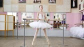 ayak parmağı : in the ballet hall, girl in white pack is engaged at the ballet, rehearse Roleve, goes up on toes, in pointe shoes , Young ballerina standing at railing in ballet hall. Stok Video