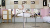 sukénka : in the ballet hall, girl in white ballet tutu, pack is engaged at ballet, rehearse part de bra with a slope, Raises hand up and down elegantly,Young ballerina standing at railing in hall.
