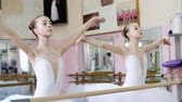 tüt : in the ballet hall, girls in white ballet tutus, packs are engaged at ballet, rehearse part de bra, Young ballerinas Raises elegantly hands up and down at railing in ballet hall.