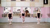 sukénka : in dancing hall, Young ballerinas in black leotards perform pas echappe, standing on toes in pointe shoes near barre at mirror in ballet class. Dostupné videozáznamy