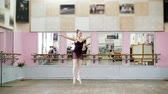 rajstopy : in dancing hall, Young ballerina in black leotard performs pas courru , pointe , She is moving through the ballet class elegantly,